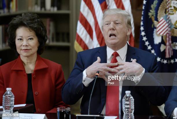 President Donald Trump speaks as Secretary of Transportation Elaine Chao looks on during a strategic and policy discussion with CEOs in the State...