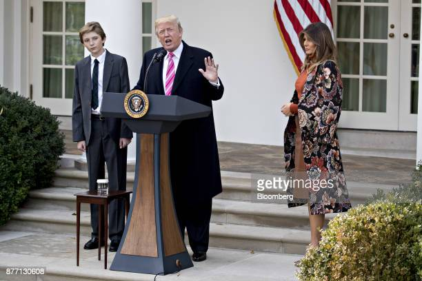 US President Donald Trump speaks as US First Lady Melania Trump right and son Barron Trump left listen before pardoning the National Thanksgiving...