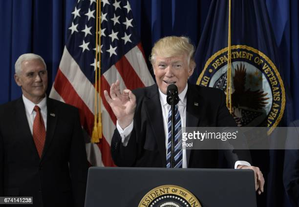 US President Donald Trump speaks as Vice President Mike Pence looks on at the Department of Veterans Affairs before signing an Executive Order on...