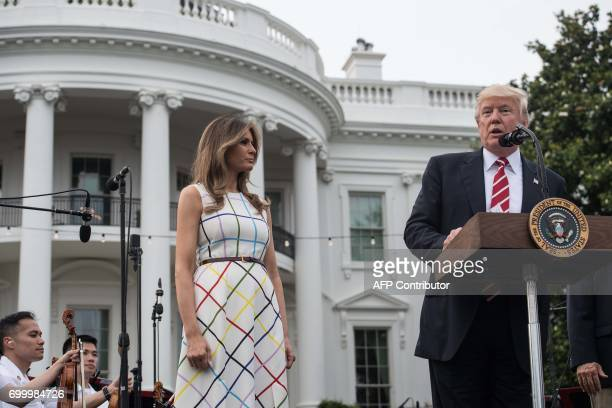 US President Donald Trump speaks at the Congressional picnic at the White House in Washington DC on June 22 2017 as First Lady Melania Trump looks on...