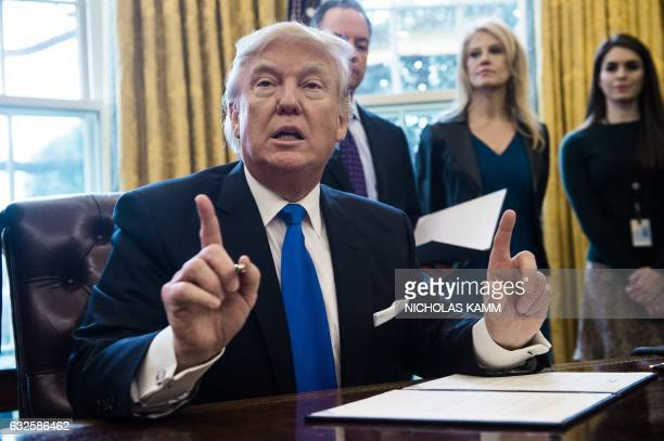 US President Donald Trump speaks before signing an executive order in the Oval Office at the White House in Washington DC on January 24 2017 US...
