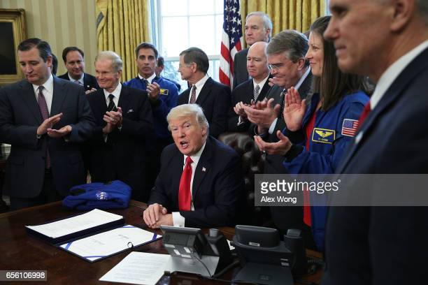 S President Donald Trump speaks during a bill signing ceremony as Vice President Mike Pence and legislators including Sen Ted Cruz Sen Bill Nelson...
