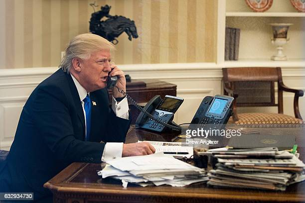 President Donald Trump speaks on the phone with Australian Prime Minister Malcolm Turnbull in the Oval Office of the White House January 28 2017 in...