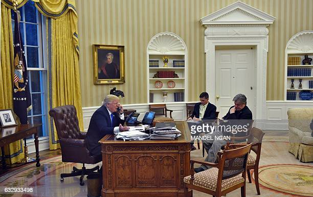 US President Donald Trump speaks on the phone with Australia's Prime Minister Malcolm Turnbull alongside Chief Strategist Steve Bannon and National...