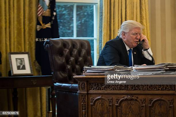 President Donald Trump speaks on the phone with Chancellor of Germany Angela Merkel in the Oval Office of the White House January 28 2017 in...