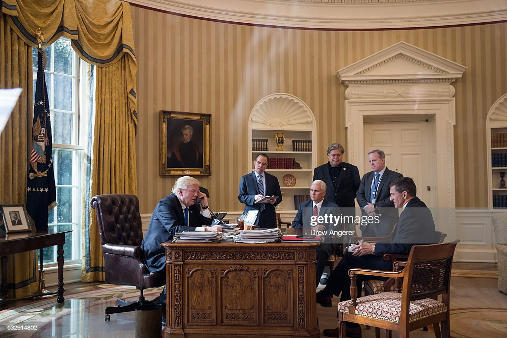 President Donald Trump speaks on the phone with Russian President Vladimir Putin in the Oval Office of the White House, January 28, 2017 in Washington, DC. Also pictured, from left, White House Chief of Staff Reince Priebus, Vice President Mike Pence, White House Chief Strategist Steve Bannon, Press Secretary Sean Spicer and National Security Advisor Michael Flynn. On Saturday, President Trump is making several phone calls with world leaders from Japan, Germany, Russia, France and Australia.