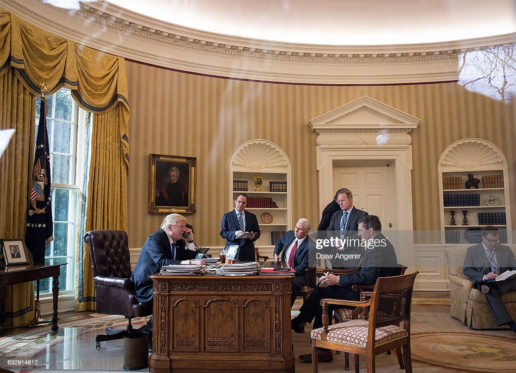 President Donald Trump speaks on the phone with Russian President Vladimir Putin in the Oval Office of the White House, January 28, 2017 in Washington, DC. Also pictured, from left, White House Chief of Staff Reince Priebus, Vice President Mike Pence, Press Secretary Sean Spicer and National Security Advisor Michael Flynn. On Saturday, President Trump is making several phone calls with world leaders from Japan, Germany, Russia, France and Australia.