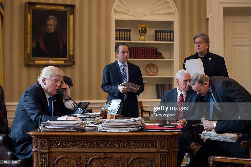 President Donald Trump speaks on the phone with Russian President Vladimir Putin in the Oval Office of the White House, January 28, 2017 in Washington, DC. Also pictured, from left, White House Chief of Staff Reince Priebus, Vice President Mike Pence, White House Chief Strategist Steve Bannon, and Press Secretary Sean Spicer. On Saturday, President Trump is making several phone calls with world leaders from Japan, Germany, Russia, France and Australia.