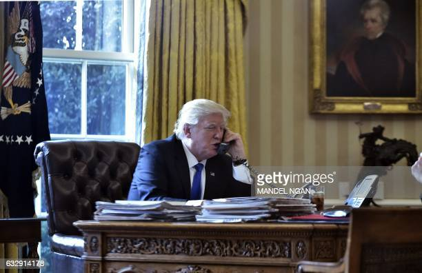 US President Donald Trump speaks on the phone with Russia's President Vladimir Putin from the Oval Office of the White House on January 28 in...