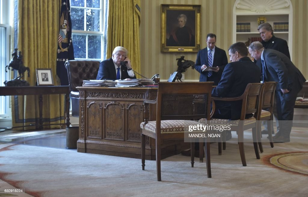 US President Donald Trump speaks on the phone with Russia's President Vladimir Putin from the Oval Office of the White House on January 28, 2017, in Washington, DC. White House Chief of Staff Reince Priebus, National Security Advisor Michael Flynn, White House Press Security Sean Spicer, and Counselor to the President Stephen Bannon. / AFP / Mandel Ngan