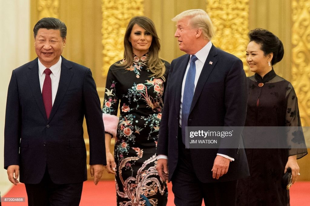 US President Donald Trump (2nd R) speaks to China's President Xi Jinping (L), as US First Lady Melania Trump (2nd L) and Xi's wife Peng Liyuan (R) look on, the Great Hall of the People in Beijing on November 9, 2017. Donald Trump urged Chinese leader Xi Jinping to work hard and act fast to help resolve the North Korean nuclear crisis during talks in Beijing Thursday, warning that 'time is quickly running out'. / AFP PHOTO / Jim WATSON