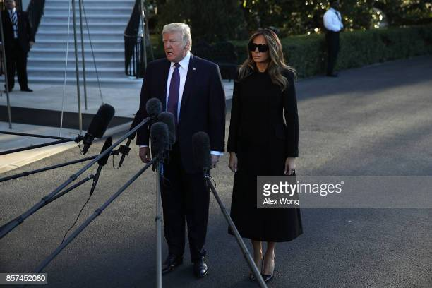 S President Donald Trump speaks to members of the media as first lady Melania Trump looks on prior to his departure from the South Lawn of the White...