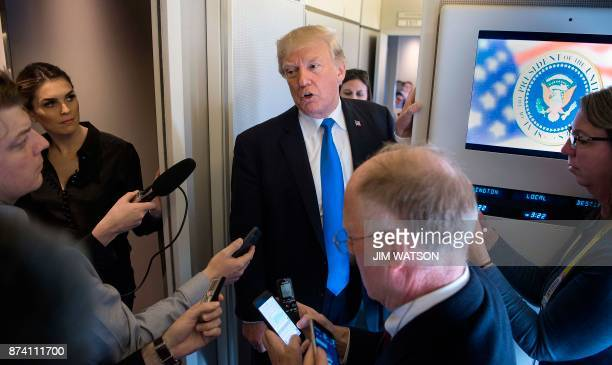 US President Donald Trump speaks to reporters aboard Air Force One while departing Manila on November 14 2017 The US president was in the Philippines...