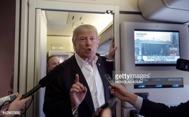 US President Donald Trump speaks to the press aboard Air Force One before addressing a rally in Melbourne Florida on February 18 2017 / AFP /...