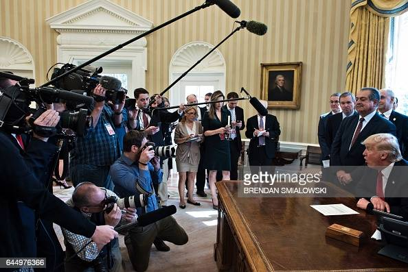 US President Donald Trump speaks to the press about an executive order on regulatory reform in the Oval Office of the White House February 24 2017 in...