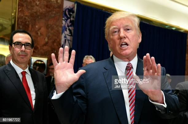 President Donald Trump speaks to the press about protests in Charlottesville after his statement on the infrastructure discussion in the lobby at...