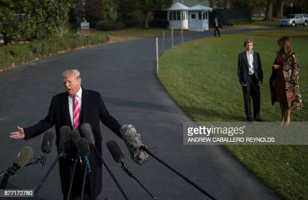 US President Donald Trump speaks to the press as First Lady Melania Trump and their son Barron look on before they departed from the south lawn of...