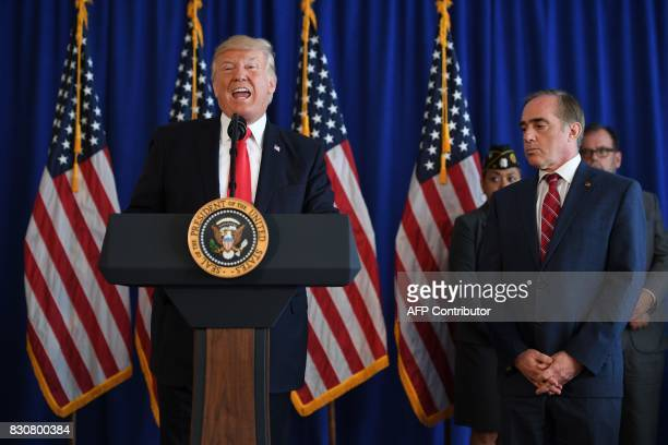 US President Donald Trump speaks to the press next to Secretary of Veterans Affairs David Shulkin before signing the Veterans Affairs Choice and...