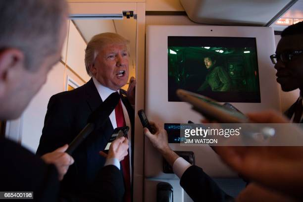 President Donald Trump speaks to the press on Air Force One on April 6 2017 Chinese President Xi Jinping touched down in Florida Thursday for a first...