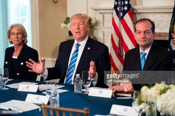 US President Donald Trump speaks to the press with US Labor Secretary Alexander Acosta and US Secretary of Education Betsy Devos on August 11 at his...