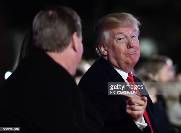 President Donald Trump speaks with US Secretary of the Interior Ryan Zinke during the 95th annual National Christmas Tree Lighting ceremony at the...