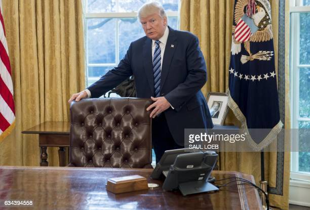 US President Donald Trump stands behind his desk after Jeff Sessions was sworn in as Attorney General in the Oval Office of the White House in...