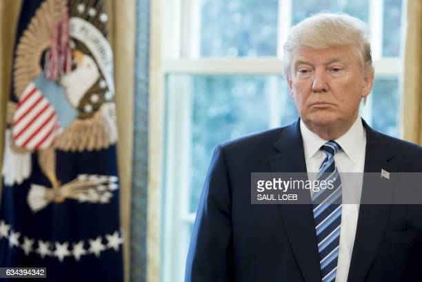 US President Donald Trump stands in the Oval Office of the White House in Washington DC February 9 following the swearingin of US Attorney General...