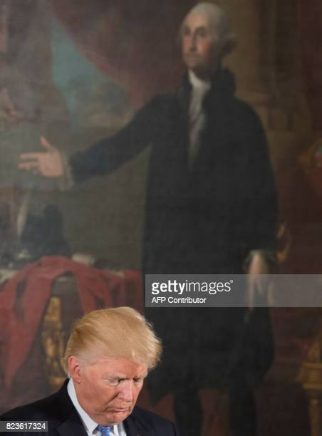 US President Donald Trump stands near a painting of US President George Washington as he presents the Medal of Valor to the first responders of the...