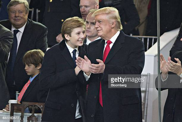 US President Donald Trump stands with his son Barron Trump in the presidential review stand outside the White House during the 58th presidential...
