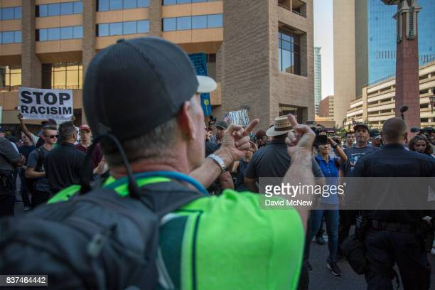 A President Donald Trump supporter makes an obscene gesture at antiTrump demonstrators outside the Phoenix Convention Center before a rally by Trump...
