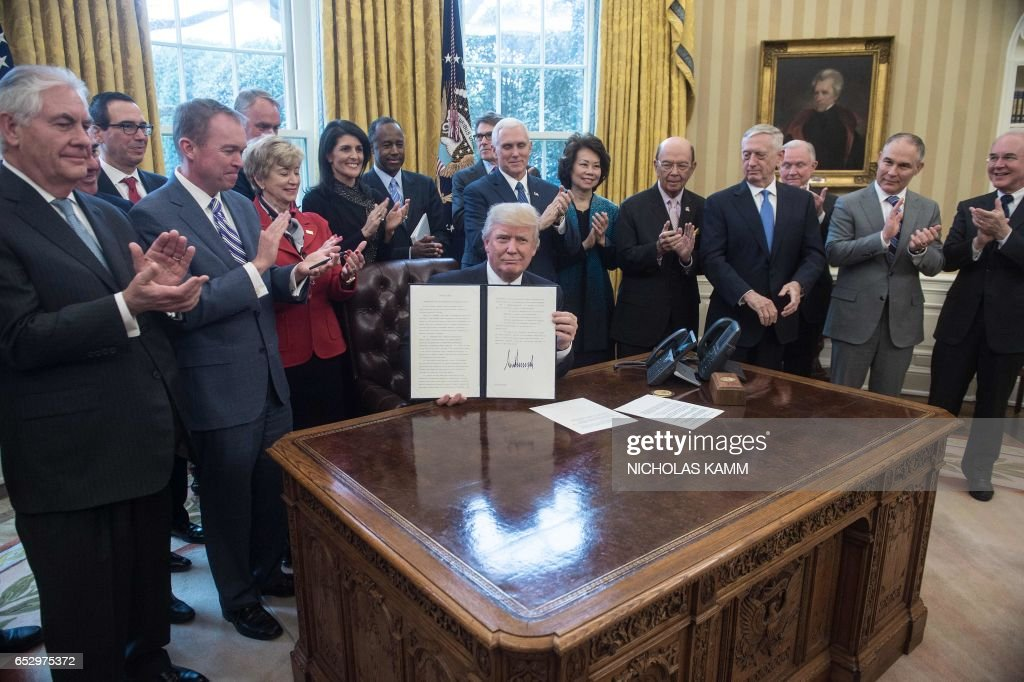 US President Donald Trump, surrounded by members of his cabinet, poses after signing an executive order entitled Comprehensive Plan for Reorganizing the Executive Branch in the Oval Office at the White House in Washington, DC, on March 13, 2017. /