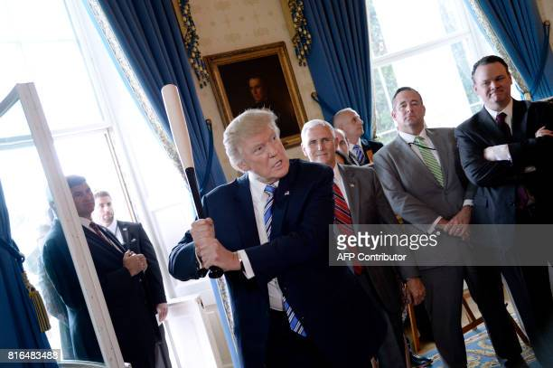 President Donald Trump swings a Marucci baseball bat in the Blue Room during a 'Made in America' product showcase event at the White House in...