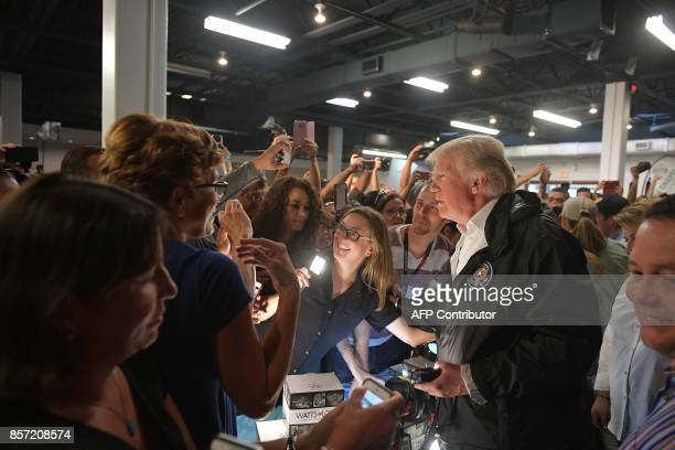 US President Donald Trump takes part in a food and suplly distribution at the Cavalry Chapel in Guaynabo Puerto Rico on October 3 2017 Nearly two...