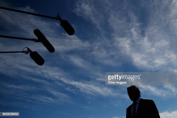 President Donald Trump takes questions from reporters before boarding Marine One on the South Lawn of the White House September 29 2017 in Washington...