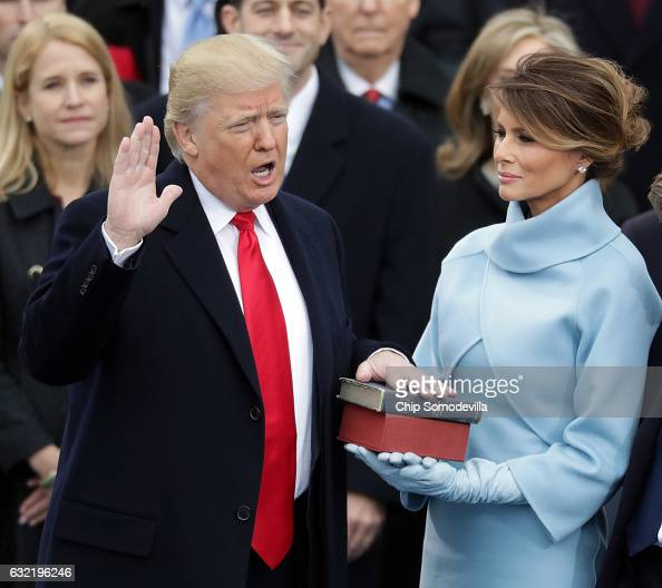 US President Donald Trump takes the oath of office as his wife Melania Trump holds the bible on the West Front of the US Capitol on January 20 2017...