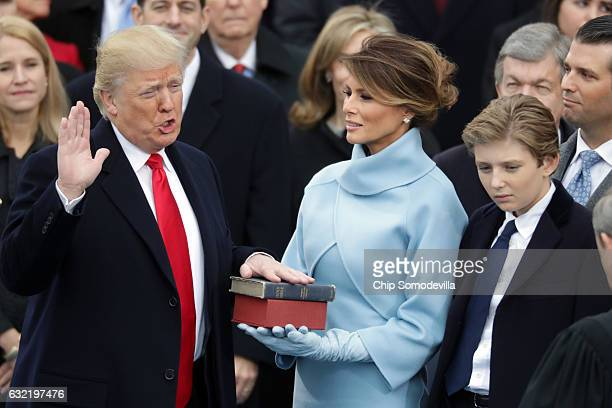 US President Donald Trump takes the oath of office as his wife Melania Trump holds the bible and his son Barron Trump looks on on the West Front of...