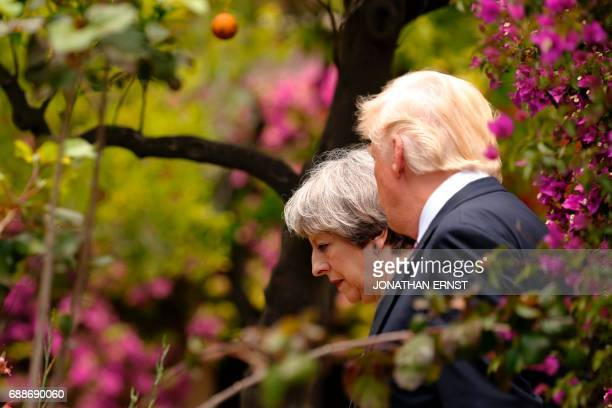 US President Donald Trump talks to Britains Prime Minister Theresa May after watching an Italian flying squadron as part of activities at the G7...