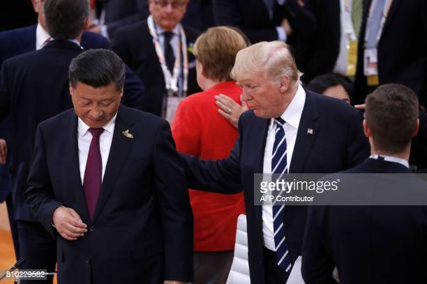US President Donald Trump talks to China's President Xi Jinping at the start of the first working session of the G20 meeting in Hamburg northern...