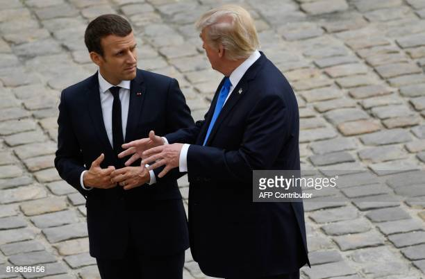 US President Donald Trump talks to French President Emmanuel Macron during a welcome ceremony at Les Invalides in Paris on July 13 2017 Donald Trump...