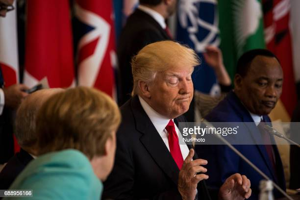 US President Donald Trump talks to German Chancellor Angela Merkel during the G7 Summit expanded session in Taormina Sicily on May 27 2017