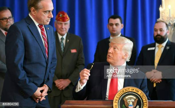 US President Donald Trump talks to Secretary of Veterans Affairs David Shulkin as he signs the Veterans Affairs Choice and Quality Employment Act on...