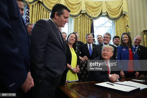 S President Donald Trump talks to Sen Ted Cruz during a bill signing ceremony in the Oval Office of the White House March 21 2017 in Washington DC...
