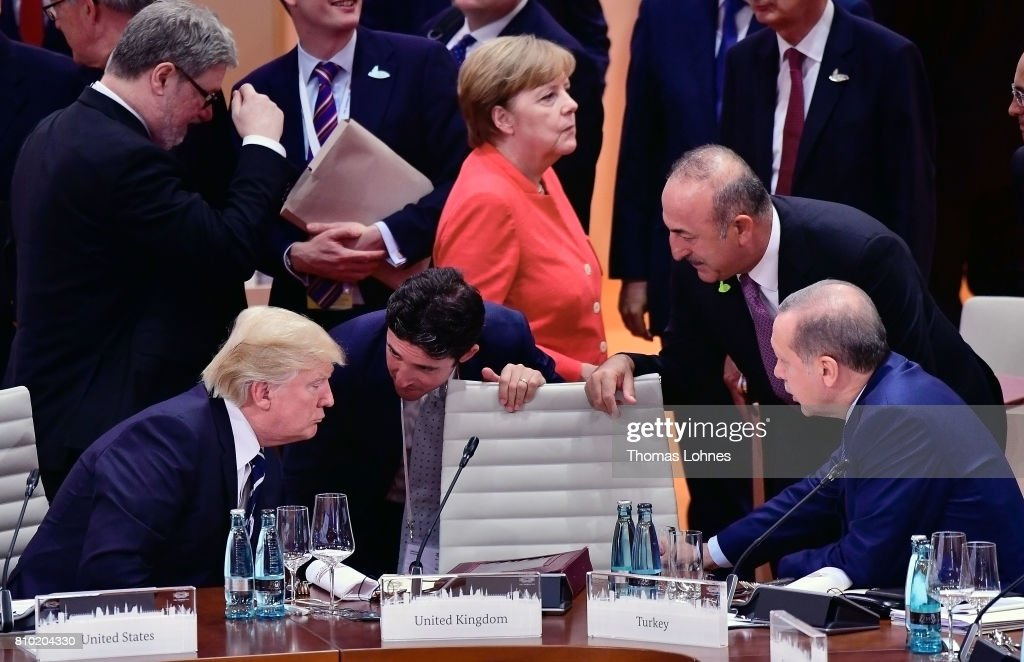 U.S. President Donald Trump (L) talks to the President of Turkey Recep Tayyip Erdogan (R) while German Chancellor Angela Merkel is seen in the background before the beginning of first working session of the G20 Nations Summit with the topic 'Global Growth and Trade' on July 7, 2017 in Hamburg, Germany.