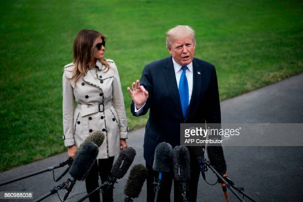 US President Donald Trump talks to the press flanked by First Lady Melania Trump as he prepares to board Marine One for Beltsville Maryland in...