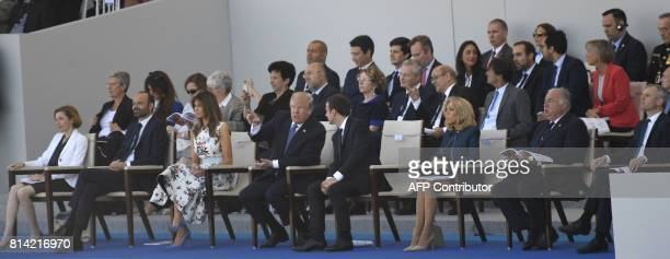 US President Donald Trump talks with French President Emmanuel Macron next to US First Lady Melania Trump French Defence Minister Florence Parly...