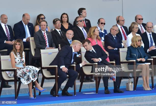 US President Donald Trump talks with his French counterpart French President Emmanuel Macron next to US First Lady Melania Trump and the French...