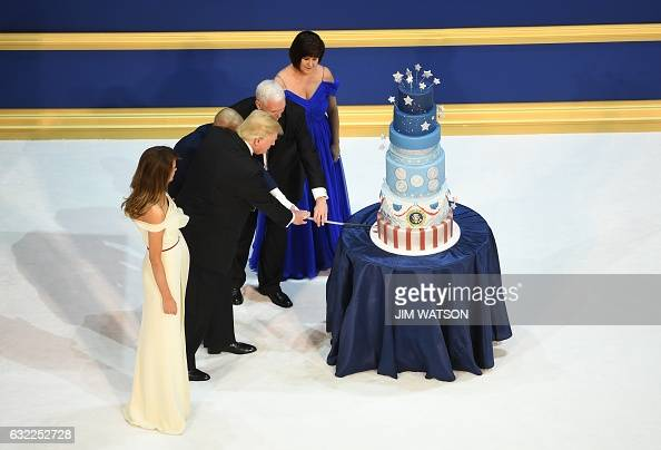 US President Donald Trump the first lady Melania Trump US Vice President Mike Pence and his wife Karen cut a cake after dancing at the Armed Services...