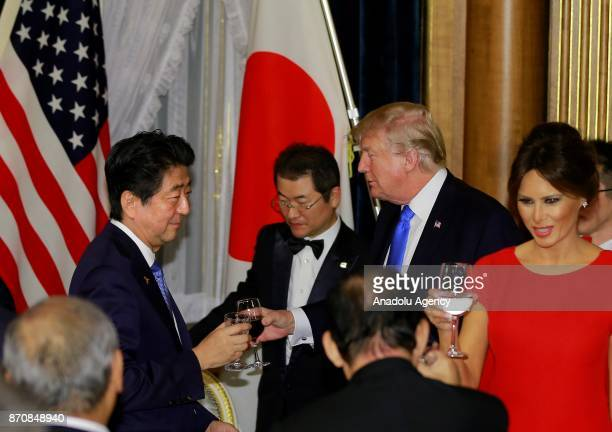 President Donald Trump toasts with Japanese Prime Minister Shinzo Abe as Mr Trump's wife Melania Trump stands next to them during a dinner hosted by...