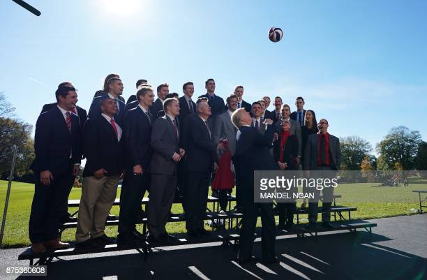 US President Donald Trump tosses a volleyball into the air while posing with members of the Ohio State Men's Volleyball team on the South Lawn of the...