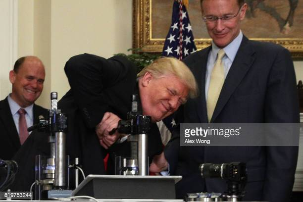 S President Donald Trump tries to break a medicine bottle with a press as Corning CEO Wendell Weeks and Rep Tom Reed look on during an announcement...